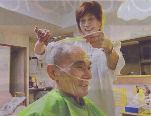 「外出が難しいので、ありかたい」。札幌市豊平区の自宅を訪れた美容師に散髪してもらい、笑顔を浮かべる長谷さん
